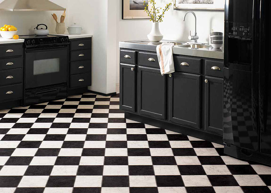 Kitchen with black cabinets and appliances on black and checkered floors, creating a high-end cafe feel.